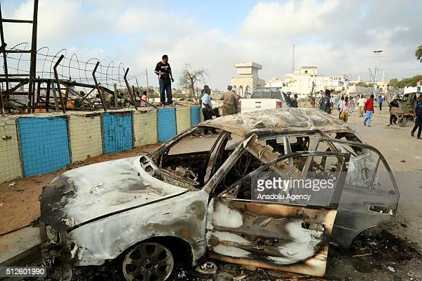 Wreckage of a car is seen after an attack in the center of Mogadishu Somalia on February 27 2016 At least 14 killed and 25 others wounded following...