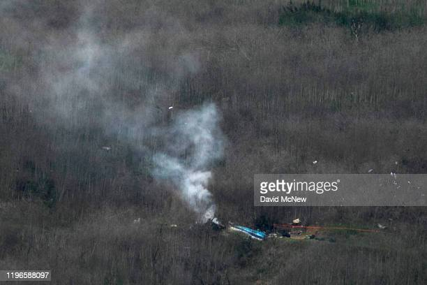 Wreckage of the crashed helicopter that was carrying former NBA star Kobe Bryant and his 13-year-old daughter Gianna smolders on the ground on...