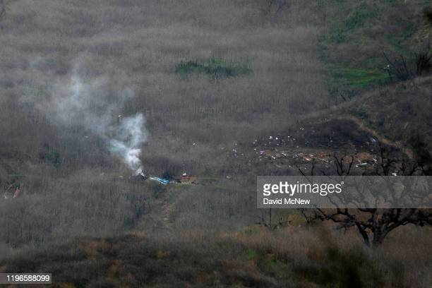 Wreckage of the crashed helicopter that was carrying former NBA star Kobe Bryant and his 13yearold daughter Gianna smolders on the ground on January...