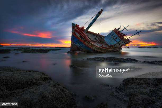 wreckage ship on the beach at twilight - sunken stock pictures, royalty-free photos & images