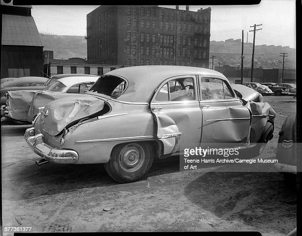 Wrecked 1949 model car driven by Norman R Allen with crumpled front end and dents on rear and passenger side parked in lot with warehouse building in...