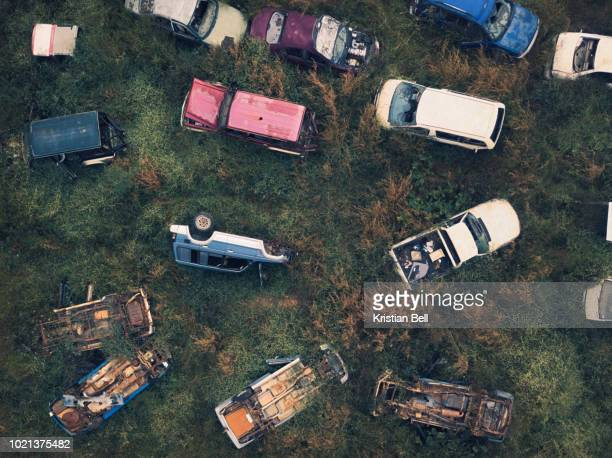 wrecked and abandoned car scrap yard in overgrown vegetation birds eye view - abandoned car stock photos and pictures