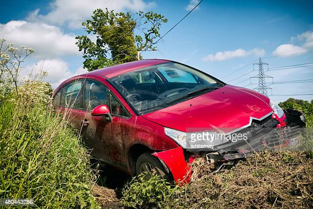 wrecked car in a roadside ditch - ditch stock photos and pictures
