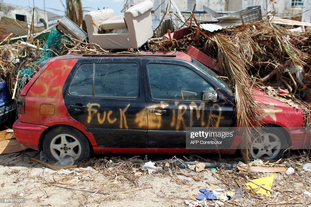 TOPSHOT - A wrecked car is seen days after this Caribbean island sustained extensive damage in the wake of Hurricane Irma in St. Martin, Friday, September 15, 2017. / AFP PHOTO / Ricardo ARDUENGO