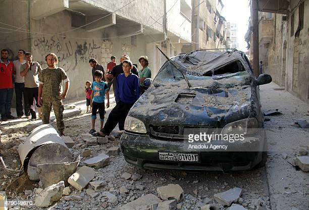 A wrecked car near damaged buildings is seen after Asad Regime Forces' barrel bomb attack on the residential areas in Bab alNairab neighborhood of...