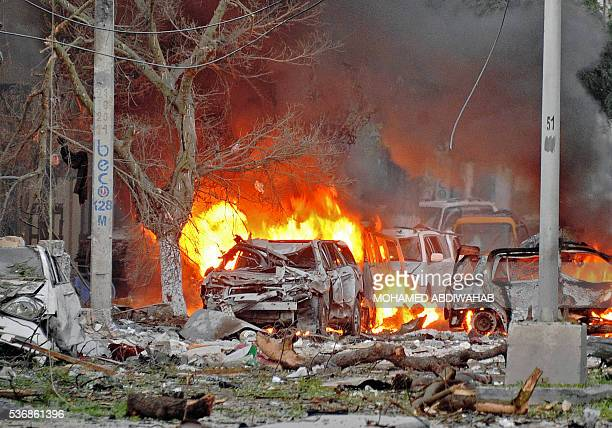 TOPSHOT Wrecked cars burn at the scene of a terror attack at the Ambassador Hotel after a car bomb exploded on June 1 2016 at a top Mogadishu hotel...
