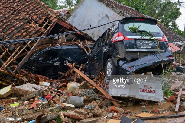 Wrecked cars lie on top of the ruins of a house destroyed by a tsunami on December 23 2018 in Carita Indonesia Over 220 people have reportedly been...