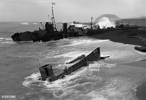 Wrecked landing craft are beached on the southeast coast of Iwo Jima A Japanese LDM lies partly beached in the background while an American LCM is...