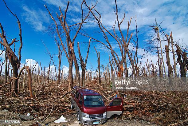 A wrecked van lies amid felled trees in Tacloban City on November 14 2013 in Tacloban Philippines Typhoon Haiyan which ripped through Philippines...