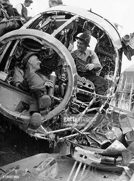 Wreckers take their lunch in the cockpit of an enemy plane at a wreckers yard August 1940