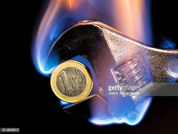 Wrench english key, holding a currency of Euro burning in flames