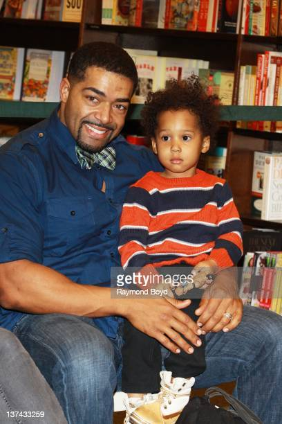 Wrestler David Otunga and his son David Otunga Jr poses for photos as his fiance and mother of his son singer and actress Jennifer Hudson signs...