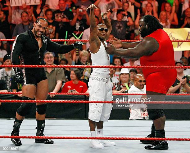 Wrestler MVP boxer Floyd Mayweather Jr and wrestler Mark Henry celebrate at the end of a tag team match during the WWE Monday Night Raw show at the...