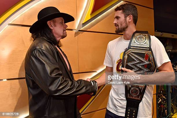 Wrestler The Undertaker shakes hands with Kevin Love of the Cleveland Cavaliers before the game against the New York Knicks on October 25 2016 at...