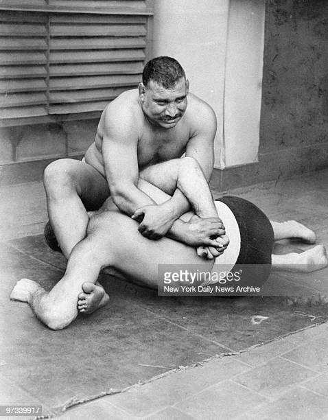 Wrestler Tiger Ali Mohammed applies a double wrist and hammerlock hold to Benny Ginsberg