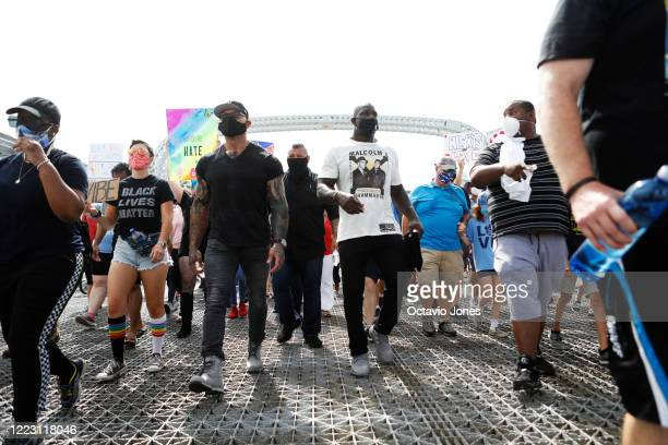 WWE wrestler Titus O'Neil and actor Dave Bautista lead the Love Walk across the Fortune Street Bridge along with several hundred supporters on June...