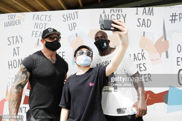 WWE wrestler Titus O'Neil and actor Dave Bautista take a selfie with fan Jake de la Cruz after the Love Walk across the Fortune Street Bridge on June...