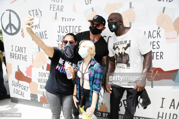 WWE wrestler Titus O'Neil and actor Dave Bautista take a selfie with their fans after the Love Walk across the Fortune Street Bridge on June 27 2020...