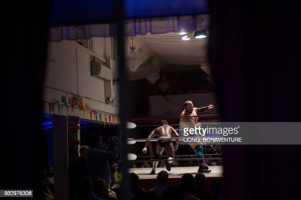 Wrestlers are pictured during a show on March 11 in Nanterre, near Paris. - In Nanterre, the French Association of Professional Wrestling revives...
