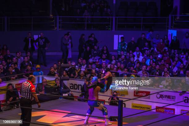 AAA wrestlers Black Danger and Ultimo Maldito perform on stage during an AAA World Wide Wrestling match on November 16 2018 in Bogota Colombia
