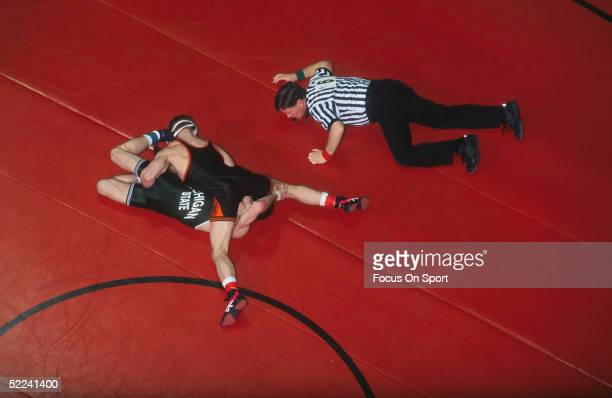 Wrestlers compete on the mat while a referee makes the count during the NCAA Division Wrestling Championships circa 1996 in Iowa City, Iowa.