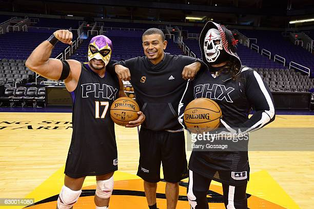 Wrestlers El Hijo Del Fantasma and La Parka poses with Earl Watson of the Phoenix Suns before the game between the Phoenix Suns and the San Antonio...