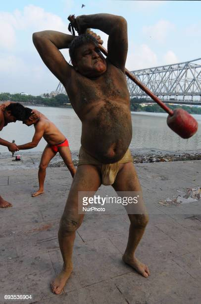 Wrestlers exercise at a traditional Indian wrestling training center on the banks of the river Ganges ahead of the Bengal mud wrestling championships...