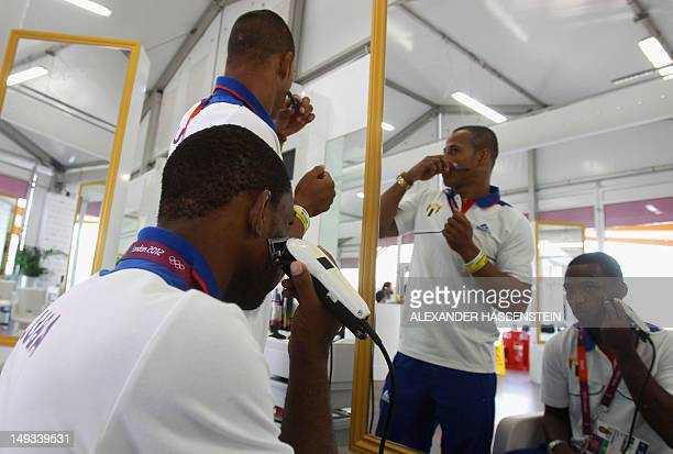 Wrestlers Hanser Meoque and Pedro Mulens of Cuba groom themselves at the Olympic village ahead of the London 2012 Olympic Games at the Olympic Park...
