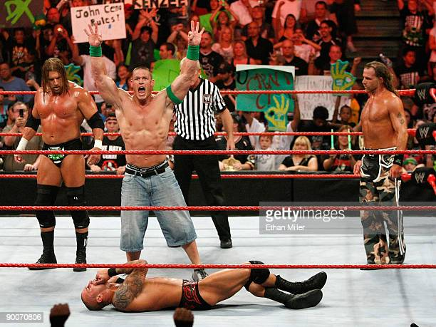 Wrestlers Triple H John Cena and Shawn Michaels celebrate as wrestler Randy Orton lies on the canvas during the WWE Monday Night Raw show at the...