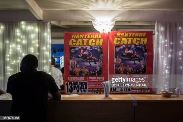 Wrestling posters advertising an upcoming event are pictured at the bar of the Studio Jenny venue on March 11 in Nanterre, near Paris. - In Nanterre,...