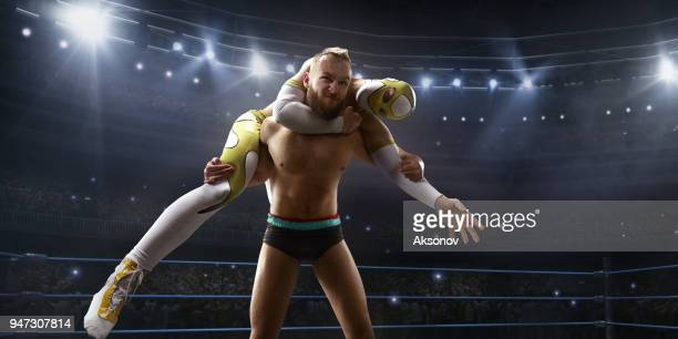 Wrestling show. Two wrestlers in a bright sport clothes and face mask fight in the ring