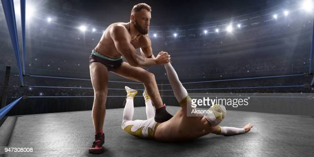 wrestling show. two wrestlers in a bright sport clothes and face mask fight in the ring - wrestling stock pictures, royalty-free photos & images