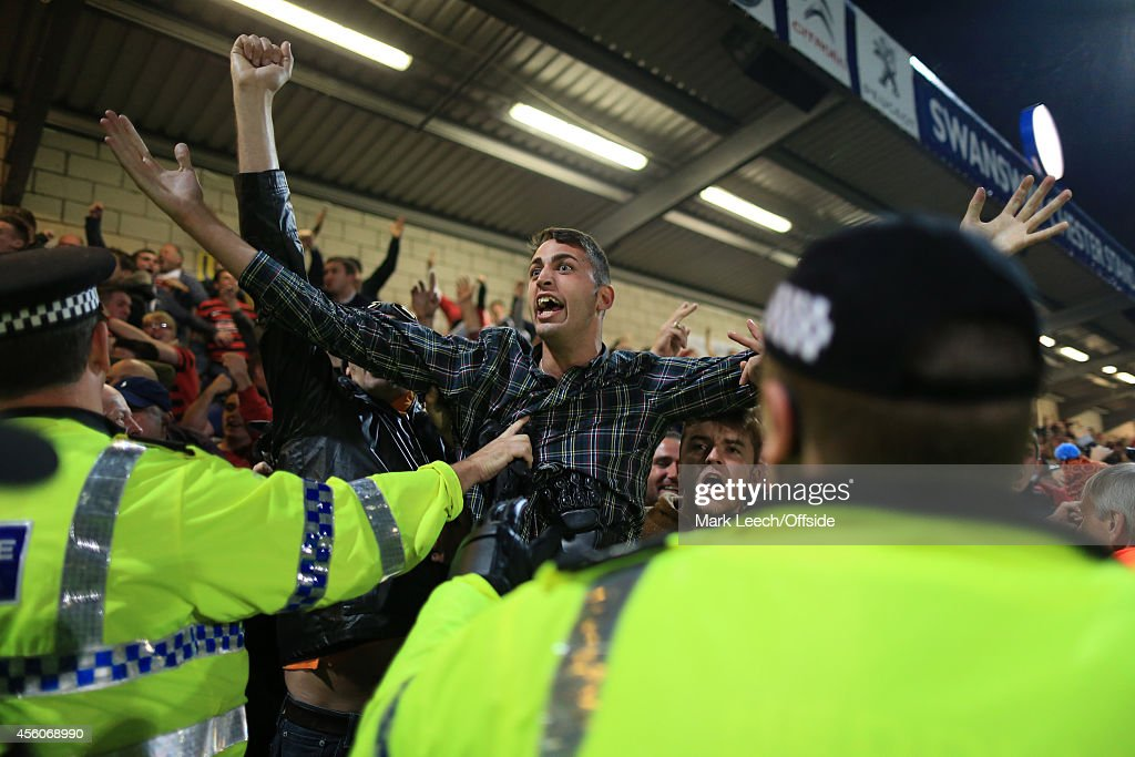 Wrexham fans celebrate their opening goal as police attempt to control them during the Vanarama Conference match between Chester and Wrexham at the Deva Stadium on September 22, 2014 in Chester, England.