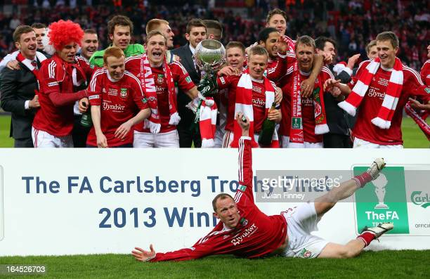 Wrexham players celebrate with the trophy as player manager Andy Morrell slides in to celebrate during the FA Trophy Final match between Wrexham and...