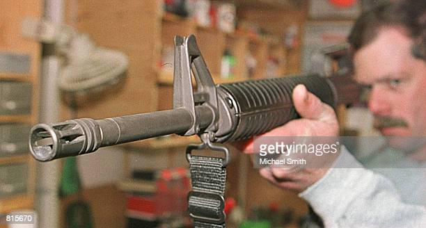 Wright Gibb looks down the barrel of an AR-15 assault rifle after cleaning it March 8, 2001 at his residence in Westminster, Co. Gibb bought a...