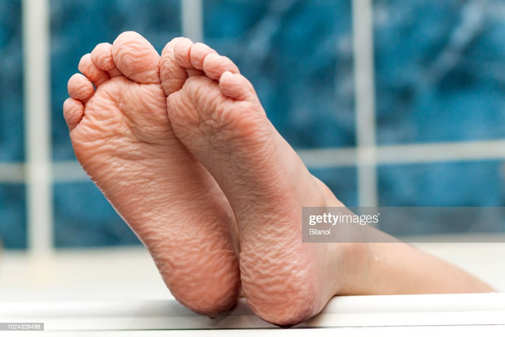 Wrinkled bare feet coming out from a bathtub. Young person getting a bath feet close-up indoor in bathroom interrior photo : Stock Photo