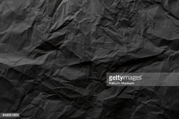Wrinkled black paper texture background