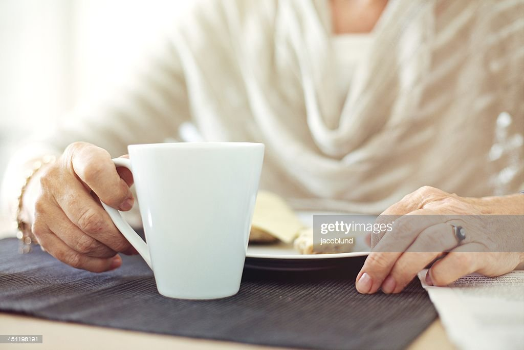 Wrinkled Hands with a Cup of Coffee : Stock Photo