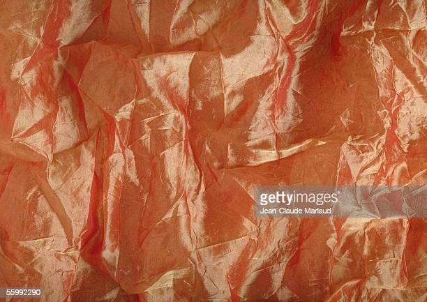 Wrinkled light orange silk, close-up, full frame