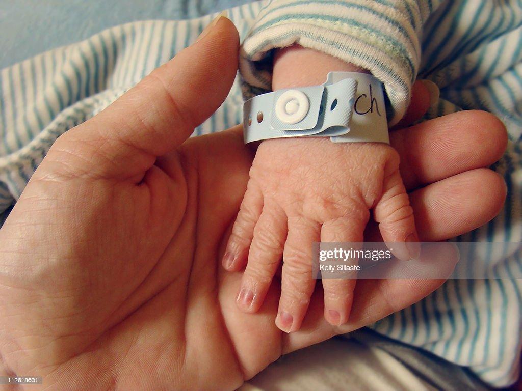 Wrinkled newborn hand with hospital bracelet : Stock Photo