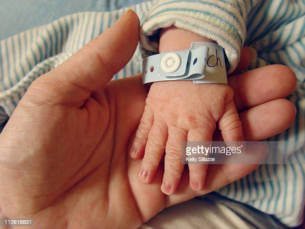 Wrinkled newborn hand with hospital bracelet