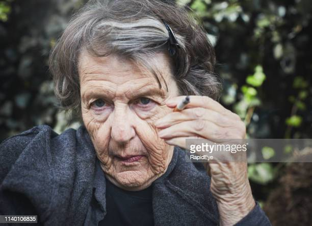 wrinkled old woman shows effects of smoking - cancer de pele imagens e fotografias de stock