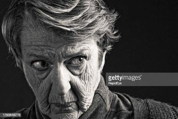 wrinkled senior woman looks anxiously to the side, in black and white - conspiracy stock pictures, royalty-free photos & images