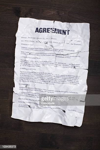 A wrinkled, torn employment agreement taped together and flattened out