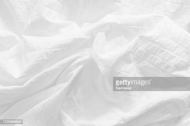 wrinkled white bedsheet - bettwäsche stock-fotos und bilder