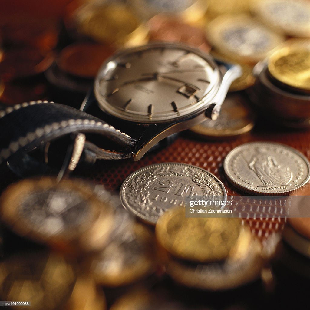 Wristwatch on top of assorted coins. : Stockfoto