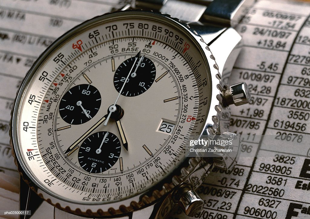 Wristwatch on top of stock report, extreme close-up : Stockfoto
