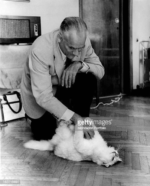 Writer Alberto Moravia pets a cat in his Roman house near Piazza del Popolo Rome November 1963