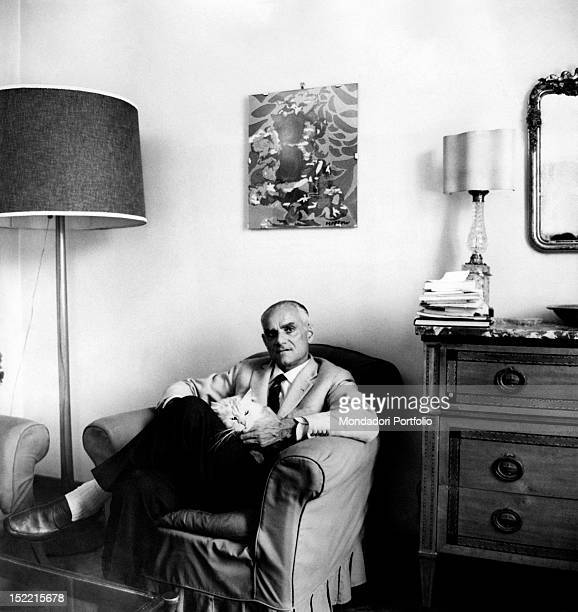 Writer Alberto Moravia seated in an armchair with a white cat in his Roman house near Piazza del Popolo Rome 1962