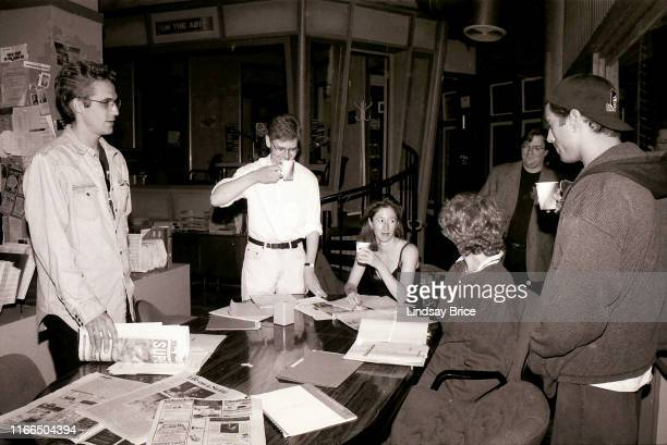 Writer and creator of NewsRadio Paul Simms and castmembers Dave Foley Vicki Lewis Stephen Root Andy Dick and Joe Rogan gather on set before table...